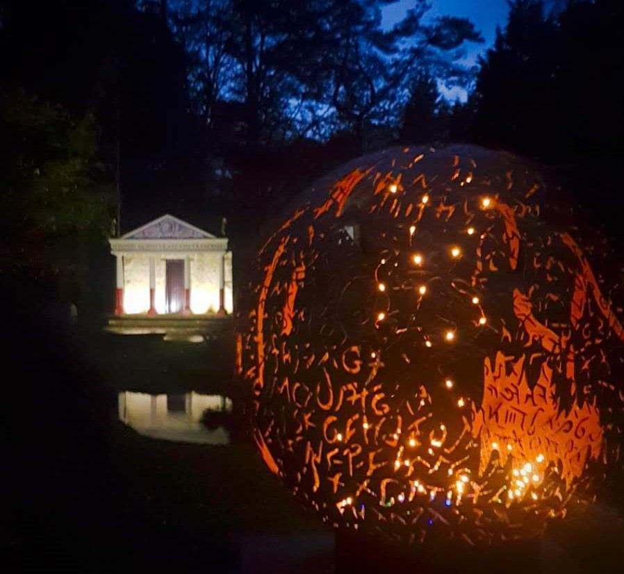 Replica roman temple and fire ball lit up at night